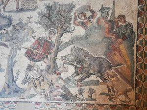 Villa romana del Casale, Sala della Piccola Caccia, dettaglio della cattura del cinghiale. In basso vi è un cacciatore a terra, ferito. Il cinghiale è spinto contro una parete rocciosa e affonda le zampe in un terreno paludoso, mentre altri cacciatori lo colpiscono dall'alto con pietre